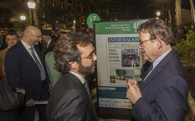El consejero delegado de Prensa Ibérica, Aitor Moll, conversa con el presidente de la Generalitat Valenciana, Ximo Puig, frente a la portada de la apertura de Terra Mítica en Benidorm, durante un instante de la inauguración de ayer de la exposición en Alicante por el cuarenta aniversario de Prensa Ibérica.