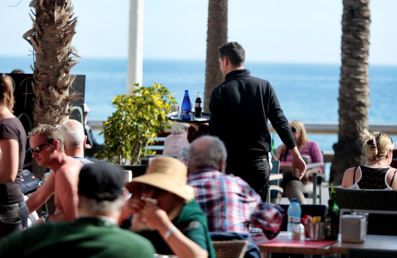 Un camarero trabaja en una terraza de Benidorm.