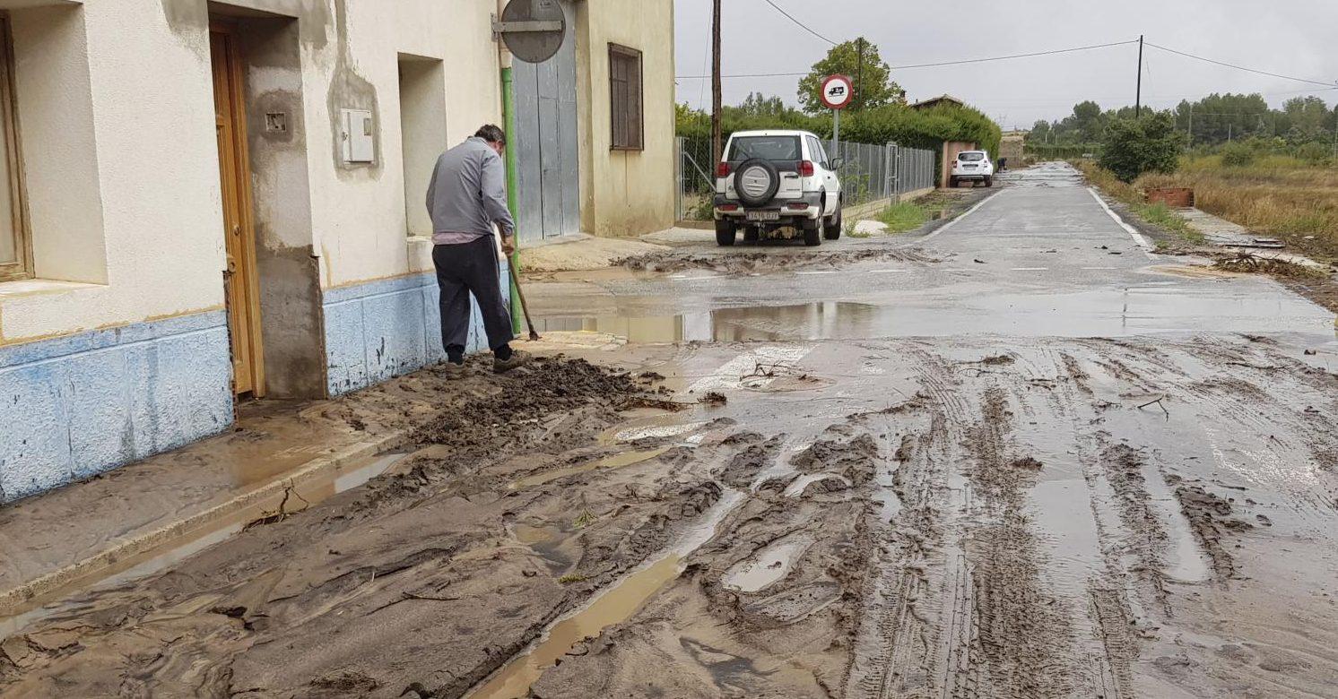 Un vecino de Beneixama limpiando la calle tras la tromba de agua.